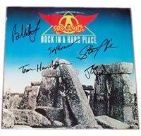 "An Aerosmith ""Rock in a Hard Place"" LP signed by Steven Tyler, Joe Perry, Brad Whitford, Joey Kramer and Tom Hamilton of Aerosmith. Album is included. Some wear is visible on album cover. Comes with Certiificate of Authenticity."